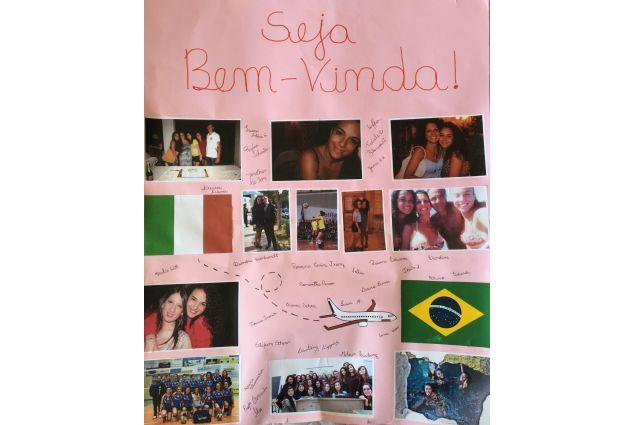 Subito la prof lì presente mi abbraccia e si presenta dandomi il benvenuto con un cartellone che i miei compagni avevano fatto per me con le mie foto e le due bandiere: del Brasile e dell'Italia! -Cristiana, Brasile